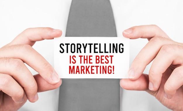 Geschäftsmann, der eine karte mit text hält geschichtenerzählen ist das beste marketing-, geschäftskonzept