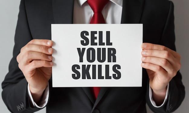 Geschäftsmann, der eine karte mit text hält verkaufen sie ihre fähigkeiten