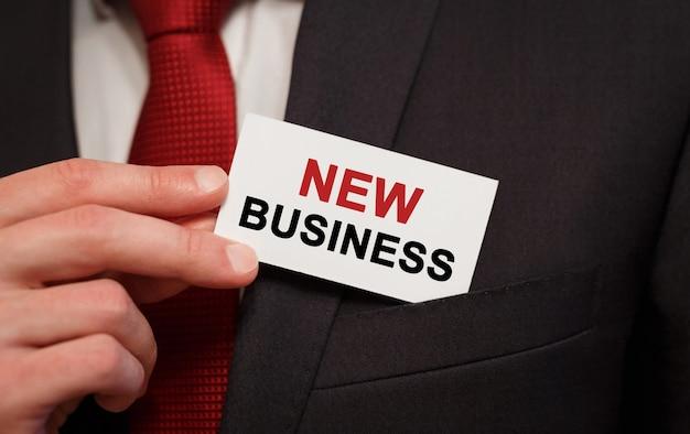 Geschäftsmann, der eine karte mit text new business in die tasche steckt