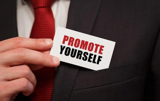 Geschäftsmann, der eine karte mit text promote yourself in die tasche steckt