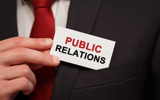 Geschäftsmann, der eine karte mit text public relations in die tasche steckt