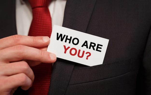 Geschäftsmann, der eine karte mit text setzt wer bist du in der tasche