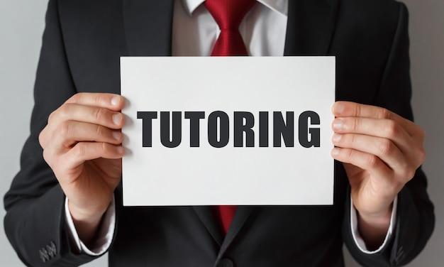 Geschäftsmann, der eine karte mit text tutoring hält