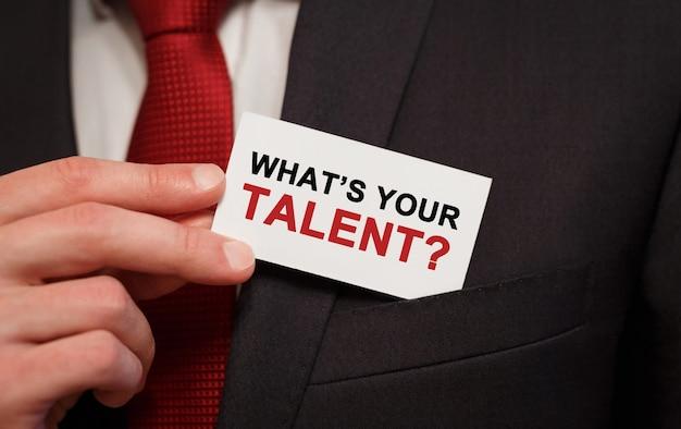 Geschäftsmann, der eine karte mit text whats your talent in die tasche steckt