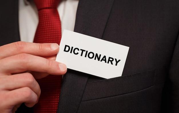 Geschäftsmann, der eine karte mit textwörterbuch in die tasche setzt