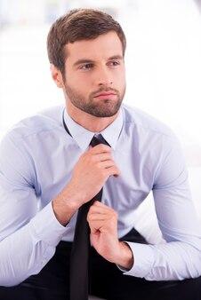 Geschäftsmann, der eine krawatte bindet. nachdenklicher junger geschäftsmann, der eine krawatte bindet, während er auf dem bett sitzt