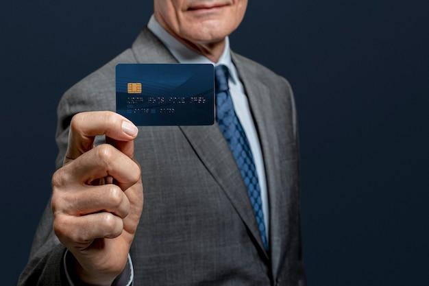 Geschäftsmann, der eine kreditkarte zeigt
