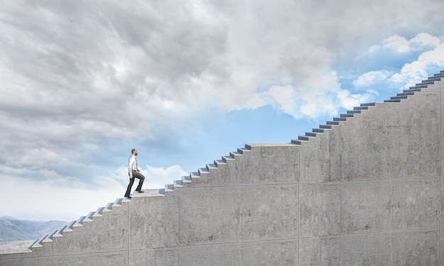 Geschäftsmann, der eine lange leiter klettert, die zum himmel führt. konzept der entschlossenheit und aspiration.