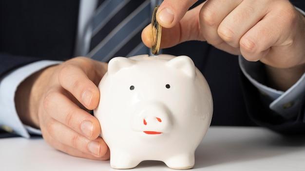 Geschäftsmann, der eine münze in ein sparschwein legt