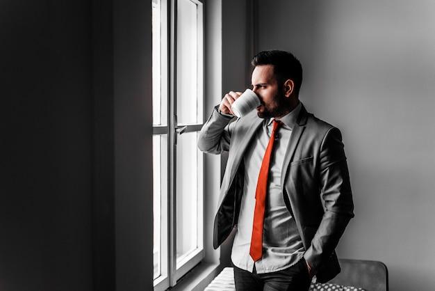 Geschäftsmann, der eine pause macht. kaffee trinken in der nähe des bürofensters.