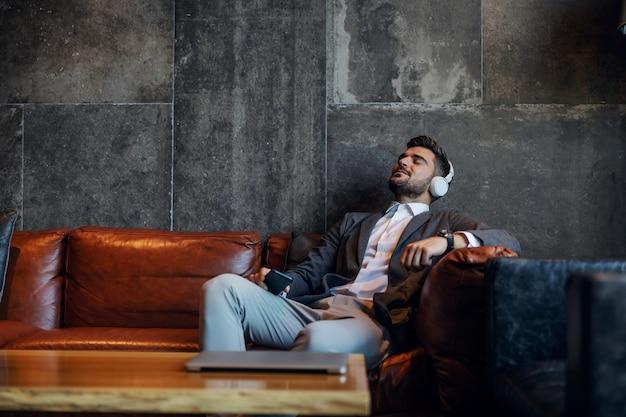 Geschäftsmann, der eine pause macht und musik genießt, während er auf einer couch in der modernen konzept-hotellobby sitzt. technologie, freizeit, zeit nehmen, ruhe