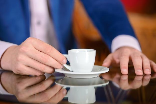 Geschäftsmann, der eine schale heißen kaffee hält.