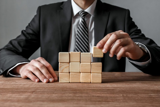 Geschäftsmann, der eine struktur mit holzwürfeln auf tisch baut. erfolgs- und geschäftsstrategiekonzept.