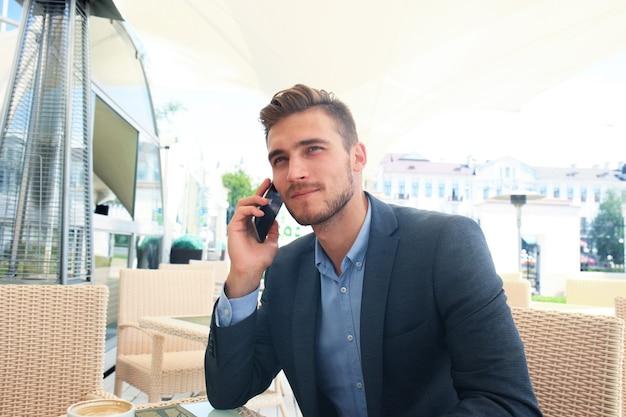 Geschäftsmann, der eine tasse kaffee trinkt, während er mit seinem telefon im café sitzt.