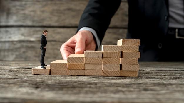 Geschäftsmann, der eine treppe baut, damit ein anderer unternehmer aufsteigen kann