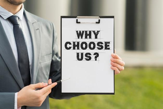 Geschäftsmann, der eine zwischenablage mit der frage hält, warum wir wählen