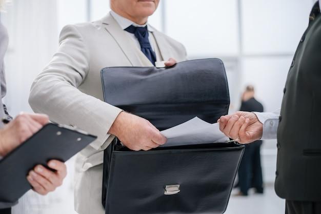 Geschäftsmann, der einem bankangestellten dokumente übergibt
