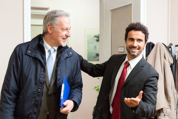 Geschäftsmann, der einen anderen geschäftsmann in seinem büro begrüßt