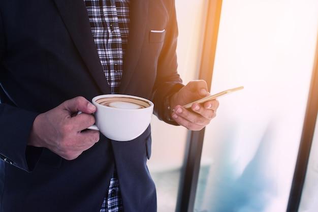 Geschäftsmann, der einen anruf unter verwendung eines intelligenten telefons mit coffeee macht