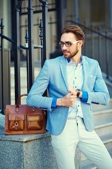 Geschäftsmann, der einen anzug auf der straße mit brauner tasche trägt