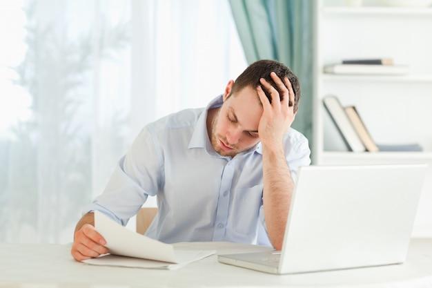 Geschäftsmann, der einen beunruhigenden buchstaben liest