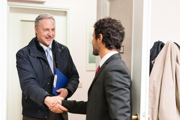 Geschäftsmann, der einen gast in seinem büro begrüßt