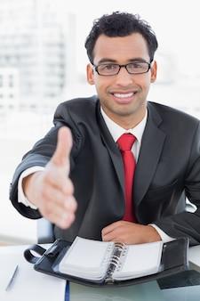 Geschäftsmann, der einen händedruck am schreibtisch anbietet