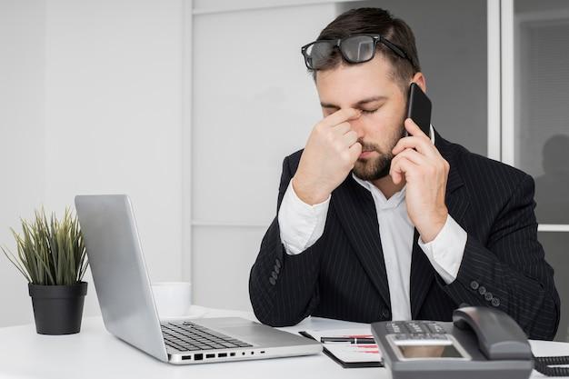 Geschäftsmann, der einen harten tag im büro hat