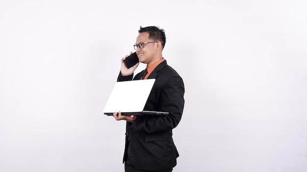 Geschäftsmann, der einen laptop-computer hält, während auf dem telefon lokalisierten weißen hintergrund