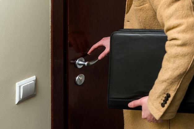Geschäftsmann, der einen luxuriösen braunen mantel trägt und leder-laptoptasche hält.