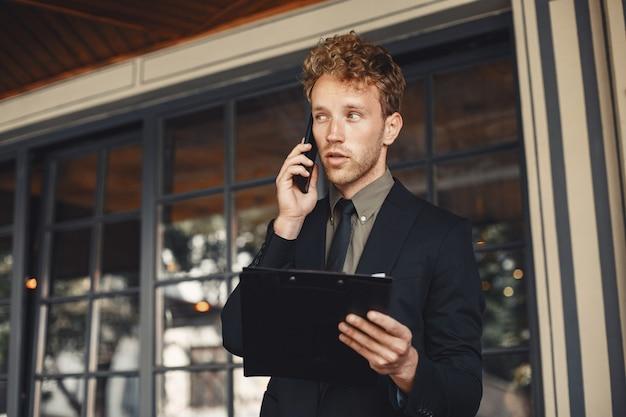 Geschäftsmann, der einen ordner in seinen händen hält. hübscher selbstbewusster geschäftsmann, der anzug stehend trägt.