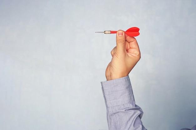 Geschäftsmann, der einen pfeil hält, der auf das ziel abzielt - business targeting, targeting, fokuskonzept. mann im blauen hemd, das darts spielt. das ziel treffen. erfolg im geschäft.