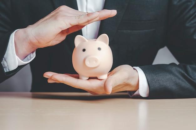 Geschäftsmann, der einen schwarzen anzug und eine versicherung trägt, um das sparschwein in der hand zu schützen konzepte der lebensversicherung.