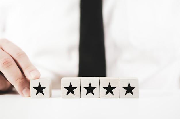 Geschäftsmann, der einen stern zu einem 5-sterne-ranking auf weißen würfeln hinzufügt