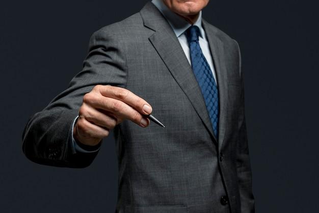 Geschäftsmann, der einen stift verwendet und auf einem unsichtbaren bildschirm unterschreibt