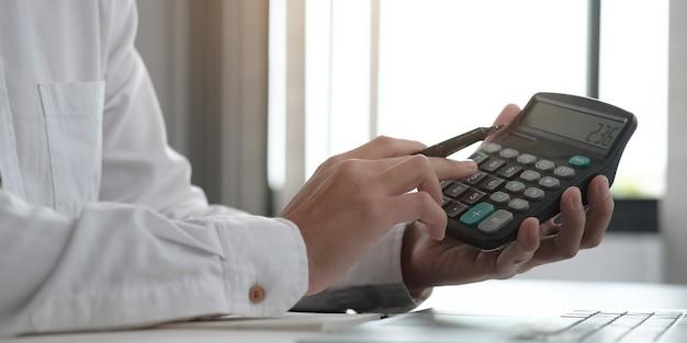 Geschäftsmann, der einen taschenrechner verwendet, um mathematische finanzen auf einem holzschreibtisch im büro zu erledigen?