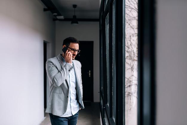 Geschäftsmann, der einen telefonanruf im bürogebäudekorridor hat