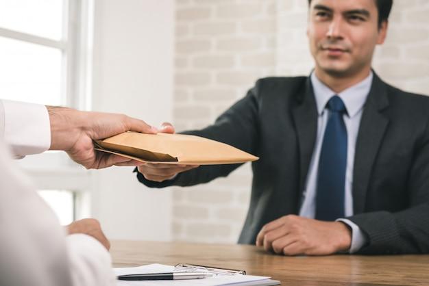 Geschäftsmann, der einen umschlag nach der vertragsunterzeichnung empfängt