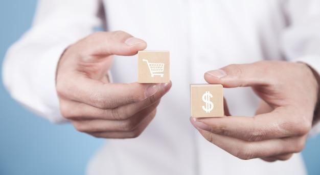 Geschäftsmann, der einkaufswagen und dollarsymbol auf holzwürfeln zeigt.