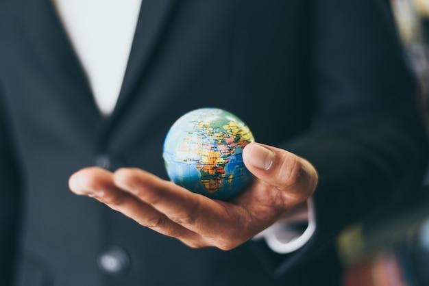 Geschäftsmann, der erdkugelmodell in der hand hält und - geschäft global und um die welt reist oder das weltkonzept rettet