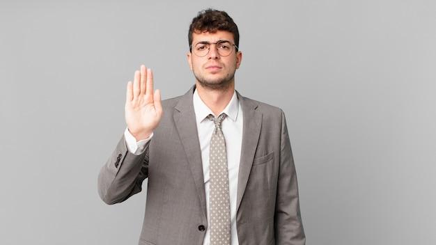 Geschäftsmann, der ernst, streng, unzufrieden und wütend aussieht und eine offene handfläche zeigt, die eine stoppgeste macht
