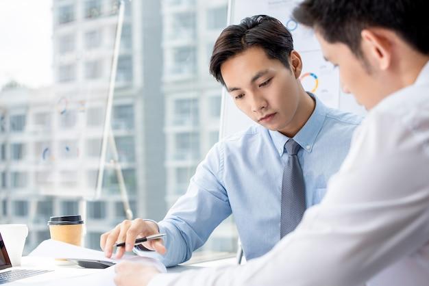 Geschäftsmann, der ernsthaft projekt mit partner im büro bespricht