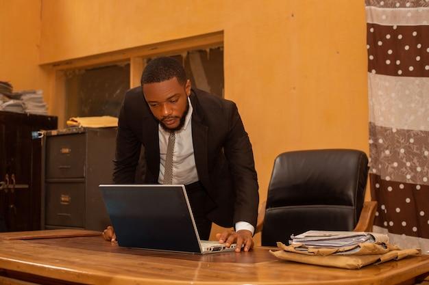 Geschäftsmann, der ernsthaft seinen laptop über den heutigen job durchgeht