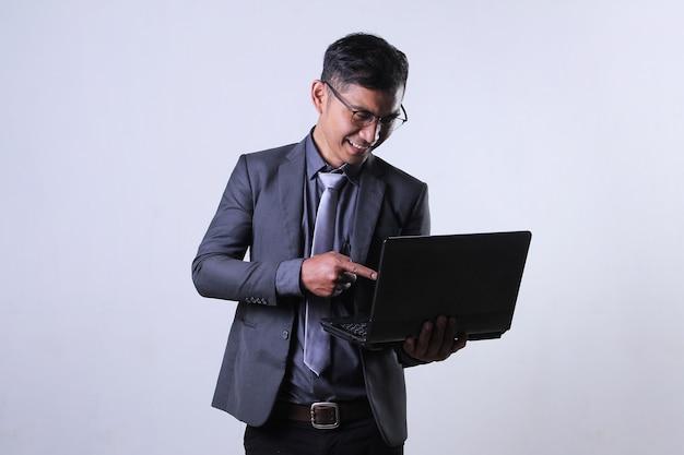 Geschäftsmann, der etwas auf einen laptop zeigt