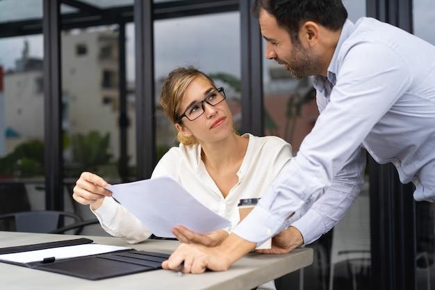 Geschäftsmann, der experten bittet, dokument zu überprüfen