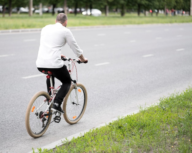 Geschäftsmann, der fahrrad auf der straße reitet