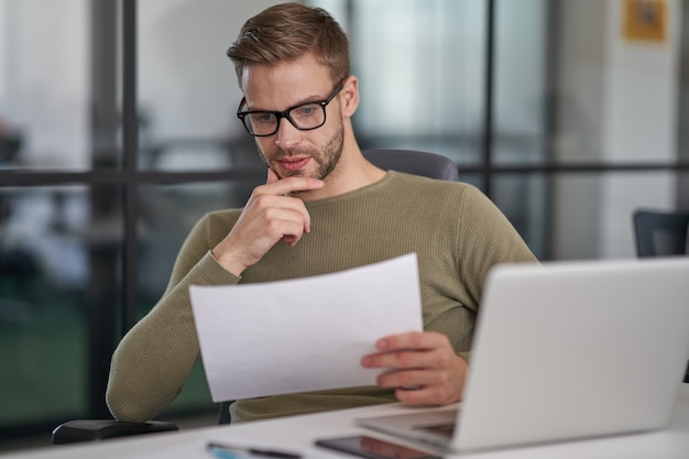 Geschäftsmann, der finanzbericht im gemütlichen kabinett liest