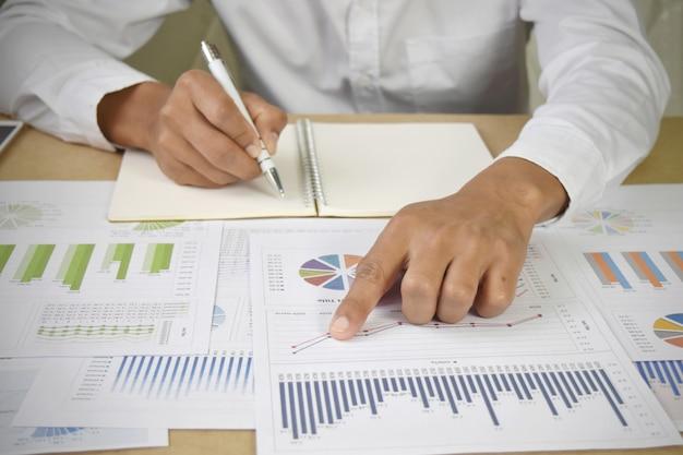 Geschäftsmann, der finanzdiagramme und diagramme auf schreibtisch analysiert