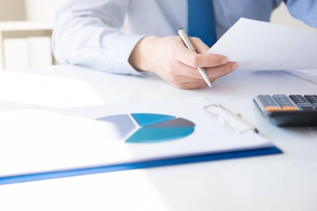 Geschäftsmann, der finanzdokument auf seinem schreibtisch hält und betrachtet