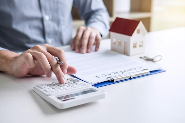 Geschäftsmann, der finanzen und berechnungskosten der immobilieninvestition tuend arbeitet, während zu unterschreiben zu unterzeichnen